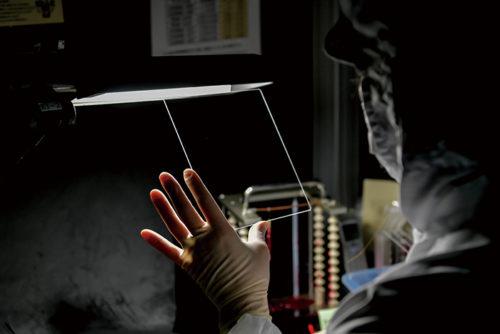 ほこりやチリを極力無くしたクリーンルームの暗室で行なう最終検査。