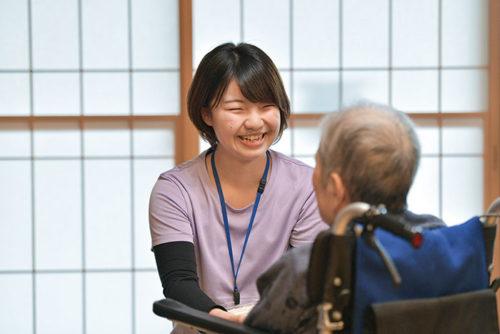 利用者様の気持ちに常に寄り添えるよう、目線を合わせて笑顔で声を掛けるスタッフ。