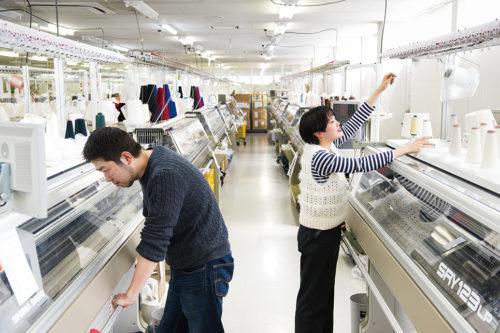 全自動横編機が計43台。日本有数の生産体制を誇る。糸からニット生地を編み立てる「編立」。開発スタッフが制作する付加価値の高いテキスタイルを複雑なプログラミングで実現。編地開発を並行して量産できる体制を構築。